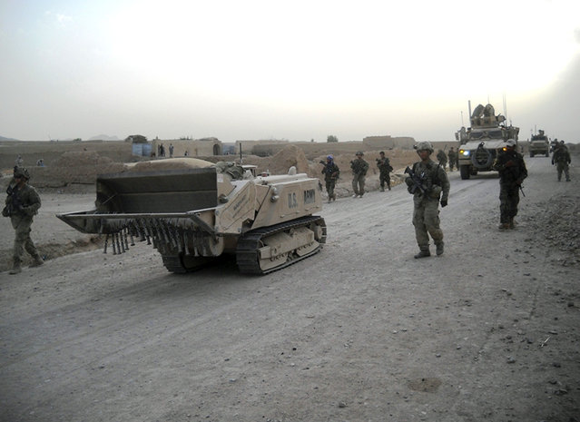 Soldiers with 3rd Brigade, 10th Mountain Division, travel alongside a Doking mine-clearance vehicle in Zharay District, Kandahar province, Afghanistan, during a recent patrol. The Doking is a remote-controlled, unmanned robotic vehicle, used for mine and route clearance. (Photo by U.S. Army)