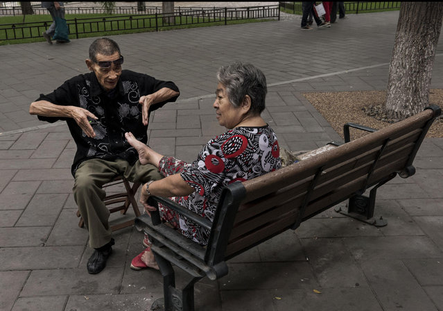 A Chinese man gestures while massaging the feet and trimming the nails of a woman at Beihai Lake area on September 12, 2014 in Beijing, China. (Photo by Kevin Frayer/Getty Images)
