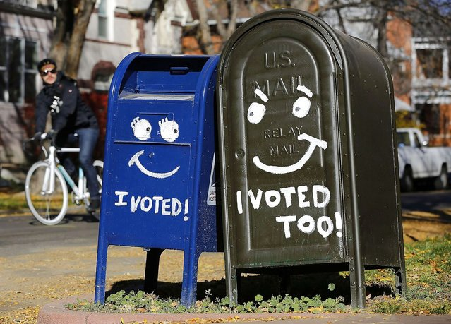 A biker passes by a pair of mailboxes in the Capitol Hill neighborhood November 6, 2012 in Denver, Colorado. Colorado is considered by most experts to be one of the key battleground state in this year's presidential election. (Photo by Marc Piscotty/AFP Photo)