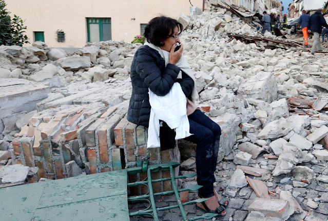 A woman sits amongst rubble following a quake in Amatrice, central Italy, August 24, 2016. (Photo by Remo Casilli/Reuters)