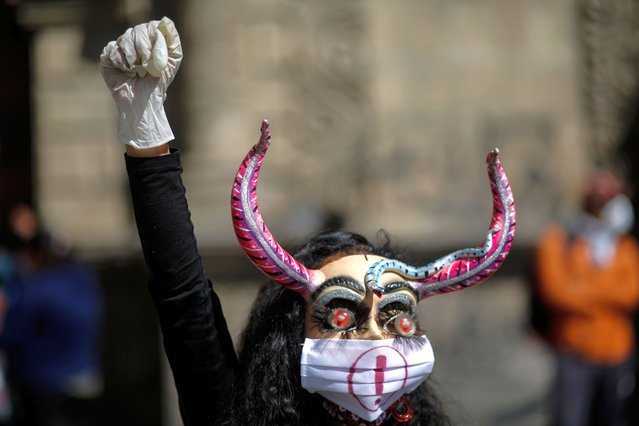 A woman wearing a traditional mask raises her fist during a protest to demand the restitution of the Ministry of Culture at San Francisco square on June 17, 2020 in La Paz, Bolivia. President of Bolivia Jeanine Añez downgraded the Ministry of Culture to a vice ministry now under the orbit of the Ministry of Education. Musicians, artists, costume manufacturers and others are also demanding government aid amid the Coronavirus lockdown. (Photo by Gaston Brito/Getty Images)