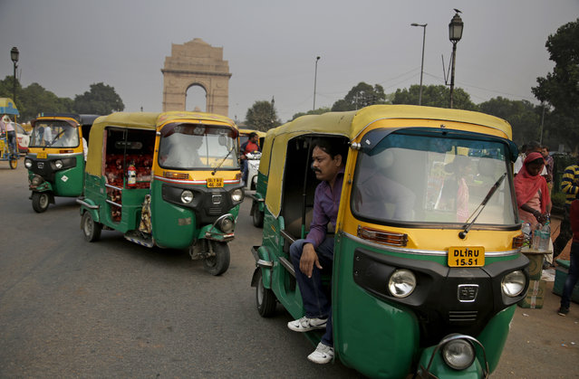"""In this November 16, 2017, photo, Sarwan Singh, an auto-rickshaw driver waits for passengers near the India Gate monument, in New Delhi, India. Singh has been ferrying passengers in his three-wheeled motorized rickshaw for 20 years, working 10 to 12 hour days. He said he thinks pollution is a problem for New Delhi but not for him personally because of his health regimen. """"I exercise every day for one hour"""", he said. """"That's why I'm strong"""". Singh said he goes for walks in the park, does yoga, drinks a lot of water and avoids oily foods. Still, he said, when the pollution gets bad, he encourages the rest of his family to stay indoors with the windows shut. """"My family is good because all the time they are at home and they don't come outside"""", he said. (Photo by Altaf Qadri/AP Photo)"""