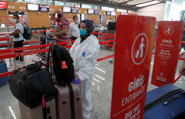 A passenger wearing a protective suit, waits to check-in for a flight to Washington D.C. at the Istanbul Airport, during the first day of resumed Turkish Airlines flights to the U.S. amid the coronavirus disease (COVID-19) outbreak, in Istanbul, Turkey on June 19, 2020. (Photo by Murad Sezer/Reuters)