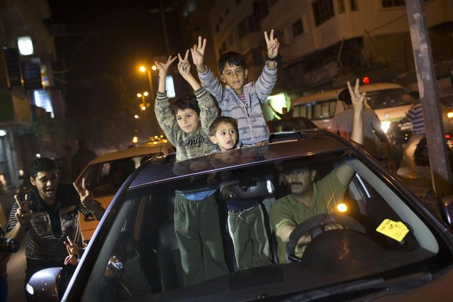 Palestinians celebrate the cease fire agreement between Israel and Hamas in Gaza City, Wednesday, November 21, 2012. Israel and the Hamas militant group agreed to a cease-fire Wednesday to end eight days of the fiercest fighting in nearly four years, promising to halt attacks on each other and ease an Israeli blockade constricting the Gaza Strip. (Photo by Adel Hana/AP)