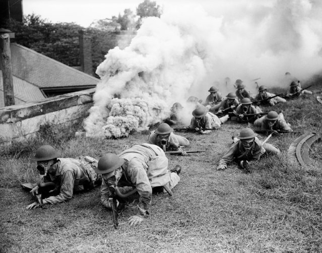 Crawling through protective smoke, U.S. troops press a Ranger-type attack upon their objective after crossing a moat, these simulated battle conditions were part of maneuvers at a U.S. eastern seaboard training center on September 22, 1942. (Photo by AP Photo)