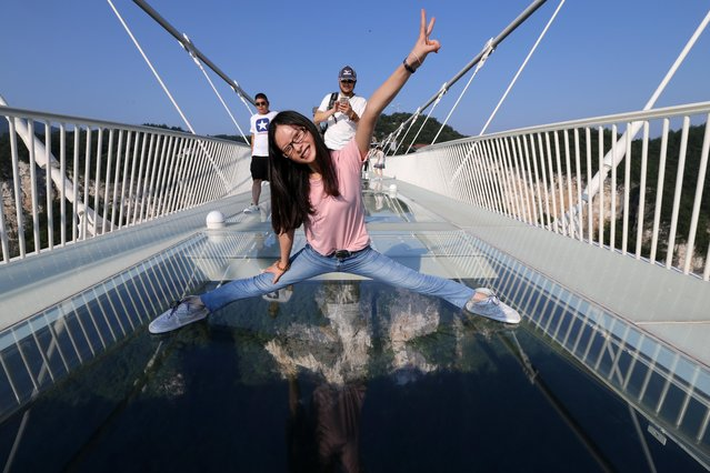 A tourist poses on the glass-bottom bridge at Zhangjiajie Grand Canyon on August 20, 2016 in Zhangjiajie, Hunan Province of China. (Photo by VCG/VCG via Getty Images)