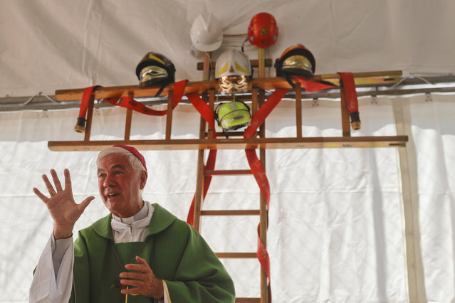 A cross made with ladders and firefighter helmets is placed inside a tent during a Mass celebrated by Bishop Giovanni D'Ercole at a tent camp set up as a temporary shelter for the earthquake survivors in Arquata Del Tronto, near Amatrice, central Italy, Sunday, August 28, 2016. (Photo by Gregorio Borgia/AP Photo)