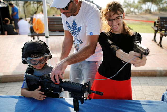 "People play with firearms during an ""open day"", exhibiting various policing skills and equipment to the public, in the southern Israeli city of Ashdod, August 29, 2016. (Photo by Amir Cohen/Reuters)"