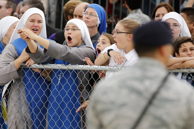 Guests show their excitement as they wait in viewing pens to see Pope Francis emerge from a private meeting with U.S. President Barack Obama upon the Pope's arrival at Joint Base Andrews outside Washington September 22, 2015. (Photo by Jonathan Ernst/Reuters)