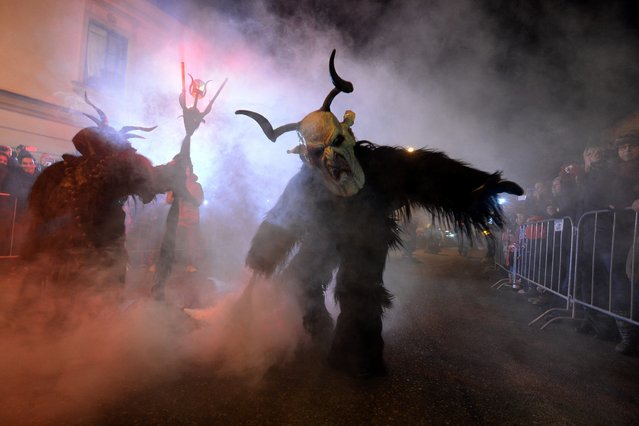 "Actors dressed as ""Krampus"" figures present a show of a traditional custom in Kaplice, South Bohemia, on December 12, 2015. The ""Krampus"" figures, who belong to a centuries old custom common in the Christmas season, traditionally are known as creatures who punish children that misbehaved. (Photo by Michal Cizek/AFP Photo)"