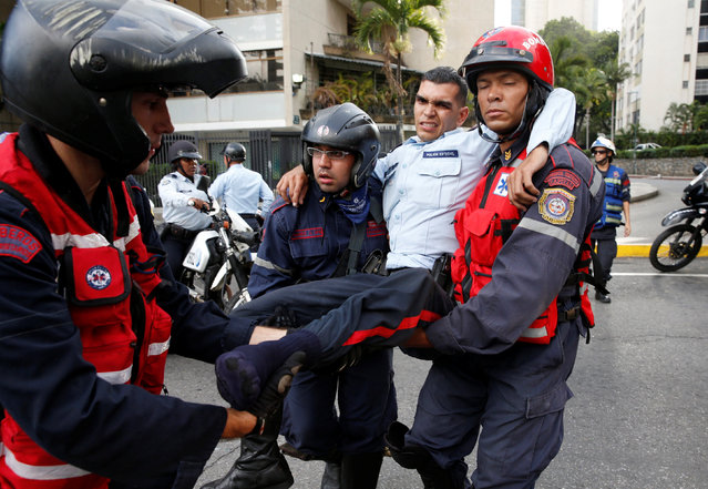 An injured police officer (2nd R) is carried by paramedics during clashes with opposition supporters after a rally to demand a referendum to remove Venezuela's President Nicolas Maduro in Caracas, Venezuela, September 1, 2016. (Photo by Carlos Garcia Rawlins/Reuters)