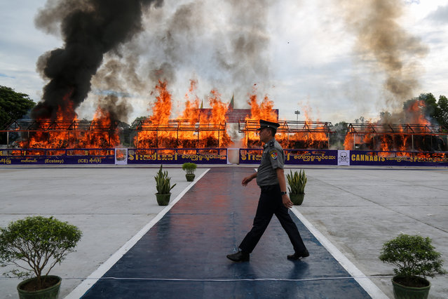 """A police officer walks in front of a burning pile of seized illegal drugs during a destruction ceremony to mark the United Nations' """"International Day against Drug Abuse and Illicit Trafficking"""" in Yangon on June 26, 2020. (Photo by Sai Aung Main/AFP Photo)"""