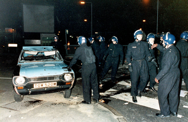 London riot police guard the Brixton district of south London on September 28, 1985, following several hours of disorders in which cars were set on fire and overturned.  Police had earlier shot and severely wounded a black woman by mistake when searching for a wanted man. (Photo by Peter Kemp/AP Photo)