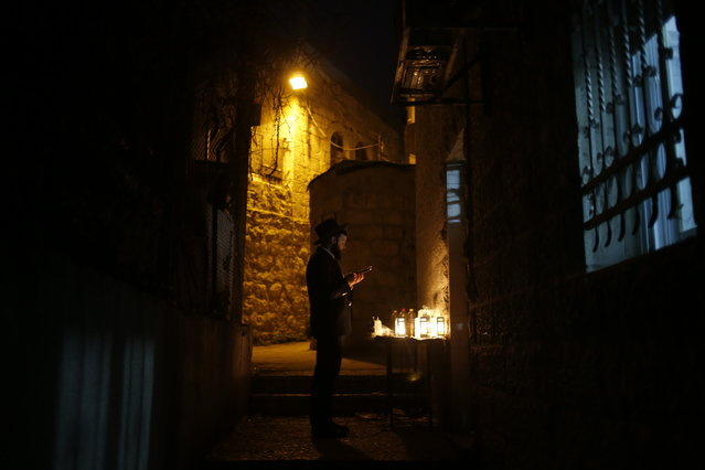 An Ultra-Orthodox Jewish man reads from a holy book among lit candles during the Jewish holiday of Hanukkah in Jerusalem's Mea Shearim neighborhood in Jerusalem, Sunday, December 17, 2017. The Jewish festival of light is an eight-day commemoration of the Jewish uprising in the second century B.C. Against the Greek-Syrian kingdom, which had tried to put statues of Greek gods in the Jewish Temple in Jerusalem. (Photo by Ariel Schalit/AP Photo)