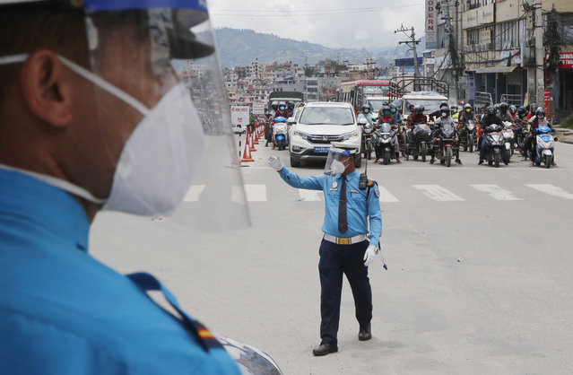 Nepalese policemen wearing masks direct traffic in Kathmandu, Nepal, Wednesday, July 22, 2020. Nepal's government has ended a lockdown 120 days after it was imposed to control the spread of coronavirus. (Photo by Niranjan Shrestha/AP Photo)