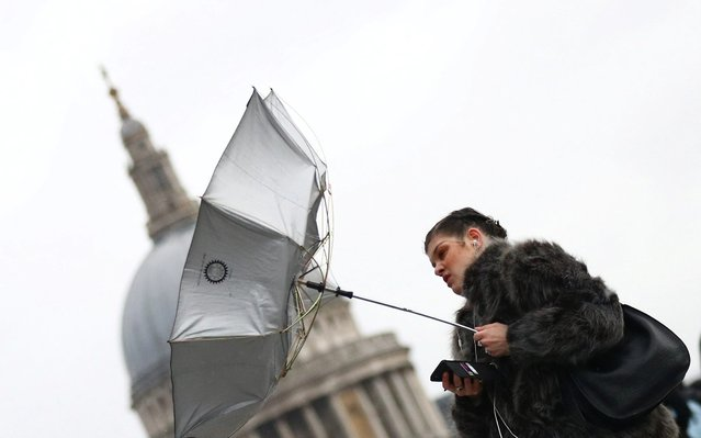 A woman struggles with an umbrella as she walks in front of St Paul's Cathedral during storm Dennis in London, Britain, February 15, 2020. (Photo by Hannah McKay/Reuters)