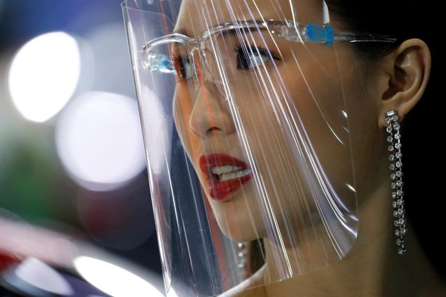 A promoter wears a face shield during the 41st Bangkok International Motor Show, after the Thai government eased measures to prevent the spread of the coronavirus disease (COVID-19), in Bangkok, Thailand, July 15, 2020. (Photo by Jorge Silva/Reuters)