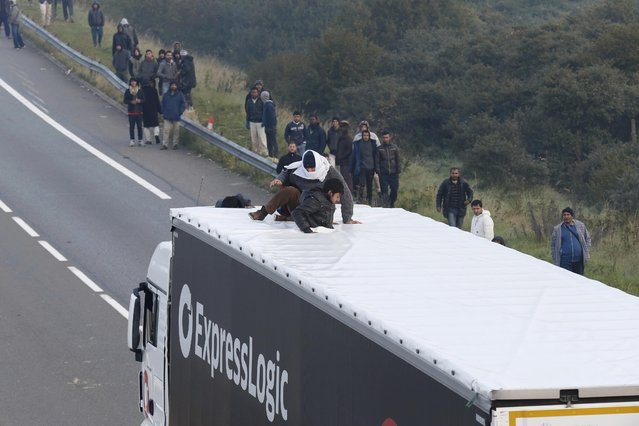 Groups of migrants gather on the road as two board a lorry on the access road to reach the ferry terminal in Calais, France, October 3, 2015. Overnight around 200 migrants tried to get into the Channel Tunnel in France, clashing with staff and police and forcing the suspension of rails services a spokesman for Eurotunnel said. (Photo by Pascal Rossignol/Reuters)
