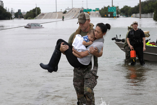 Houston Police SWAT officer Daryl Hudeck carries Catherine Pham and her 13-month-old son Aiden after rescuing them from their home surrounded by floodwaters from Tropical Storm Harvey in Houston on August 27, 2017. (Photo by David J. Phillip/AP Photo)