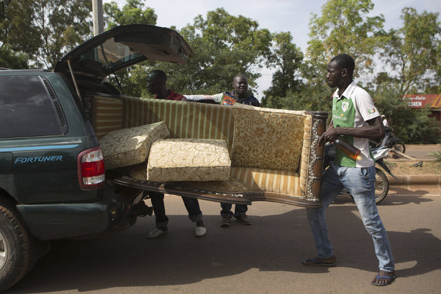People carry a couch looted from the house belonging to Francois, younger brother of Burkina Faso's ex-President Blaise Compaore, in Ouagadougou, capital of Burkina Faso, October 31, 2014. (Photo by Joe Penney/Reuters)
