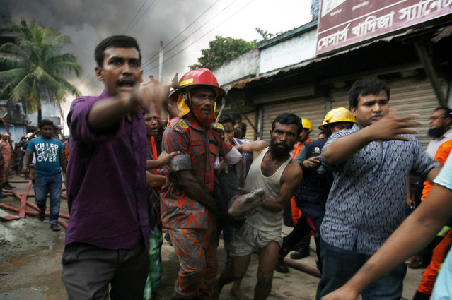 A Bangladeshi rescue worker and a volunteer carry the body of a victim from the site of an explosion in a factory in the key Bangladeshi garment manufacturing town of Tongi, just north of the capital Dhaka, on September 10, 2016. (Photo by AFP Photo/Stringer)