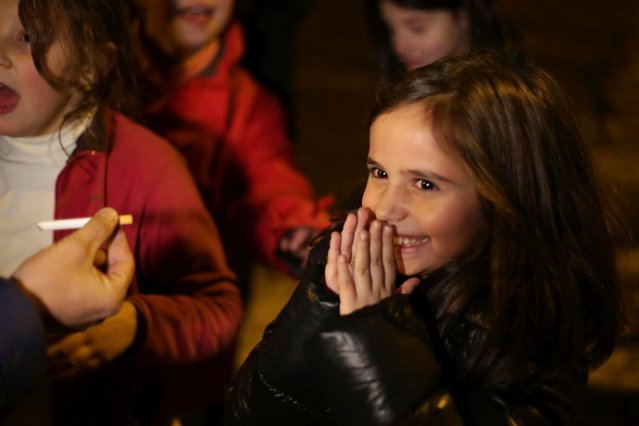 Ines, 8 years old, reacts as her father Frederico hands her her first cigarette, in the village of Vale de Salgueiro, northern Portugal, during the local Kings' Feast Friday, January 5, 2018. (Photo by Armando Franca/AP Photo)