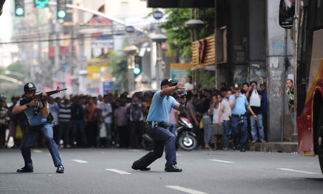 Filipino policemen aim their guns towards a hostage-taker, not shown, inside a passenger bus as the crowd watches, in Manila, Philippines, Thursday October 8, 2015. Passengers jumped out on one of the windows of the bus as the man armed with an ice pick declared the hostage-taking. He later died at the hospital after being gunned down by police. (Photo by AP Photo)