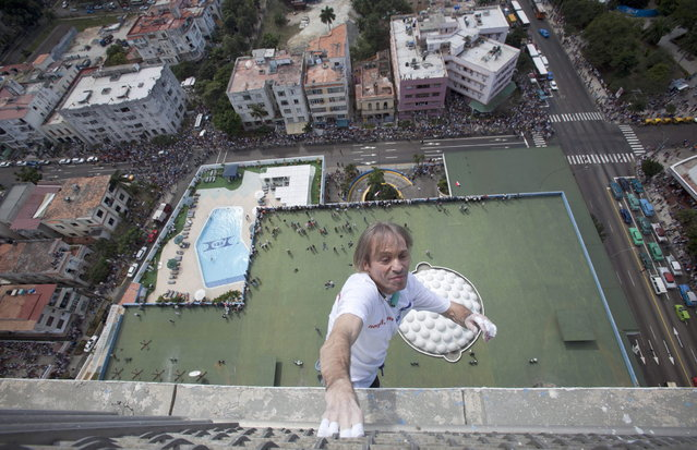 Curious tourists and locals watch from below as French daredevil Alain Robert scales the Habana Libre hotel without using ropes or a safety net, in Havana, Cuba, Monday, February 4, 2013. Once the city's Hilton, Robert was able to reach the top of the 27-story building in 30 minutes. Robert has scaled much taller buildings in his career. He says his main concern is that the hotel is in disrepair like other Havana landmarks. (AP Photo/Ramon Espinosa, Pool)