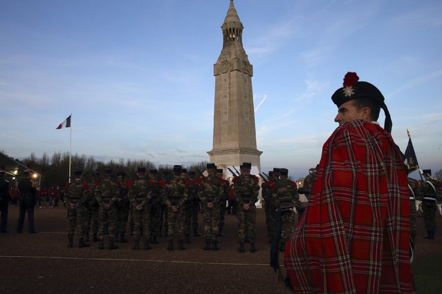 A piper of Normandy Highlands Pipe attends a ceremony to inaugurate the new war memorial at Notre Dame de Lorette, an elliptical ring engraved with the names of the 580,000 men who died in northern France during the First World War, in Ablain-Saint-Nazaire November 11, 2014. (Photo by Pascal Rossignol/Reuters)