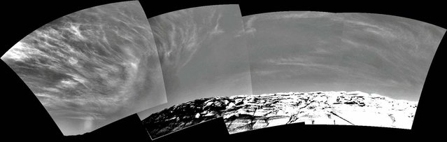 Clouds appear in the Martian sky above Endurance Crater in this mosaic of frames taken by the navigation camera on NASA's Rover Opportunity at about 9:30 a.m. on the rover's 290th sol (November 16, 2004). These clouds are part of a band that forms near the equator when Mars is near the part of its orbit that is farthest from the Sun. (Photo by AP Photo/NASA/JPL/The Atlantic)