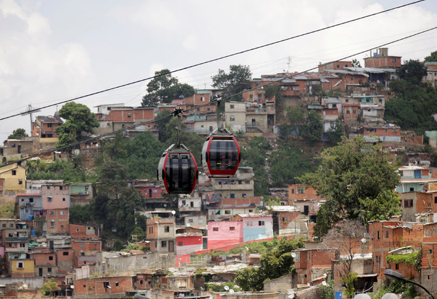 Commuters travel in a Metrocable cabin over the neighbourhood of San Agustin in Caracas, Venezuela September 12, 2016. (Photo by Henry Romero/Reuters)