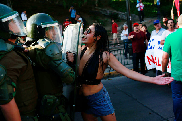 A demonstrator confronts riot police during a rally in defense of the nationalization of lithium reserves in the country, in Santiago, Chile on January 29, 2018. (Photo by Pablo Sanhueza/Reuters)