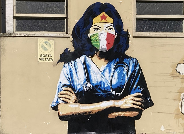 A Wonder Woman medic wearing a face mask with the colors of the Italian flag is painted on a wall in Codogno, the northern Italian town that recorded Italy's first locally spread coronavirus infection, Sunday, August 30, 2020. (Photo by Karl Ritter/AP Photo)