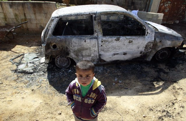 A Palestinian boy stands near a burnt car in the West Bank village of Kusra near Nablus February 21, 2013. Six Palestinian-owned cars were damaged in the West Bank village overnight, in what residents said was an attack by settlers from a near-by Jewish outpost. The Israeli army said it had received a complaint and is now investigating the incident. (Photo by Ammar Awad/Reuters)