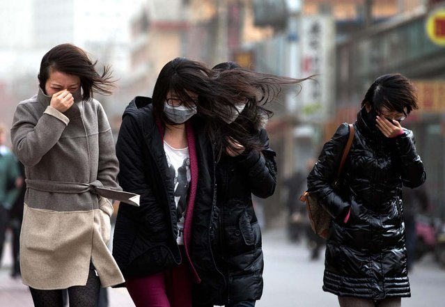 Chinese women, some wearing face masks, brace through strong wind after the capital city is hit by sandstorm in Beijing Thursday, February 28, 2013. (Photo by Andy Wong/AP Photo)