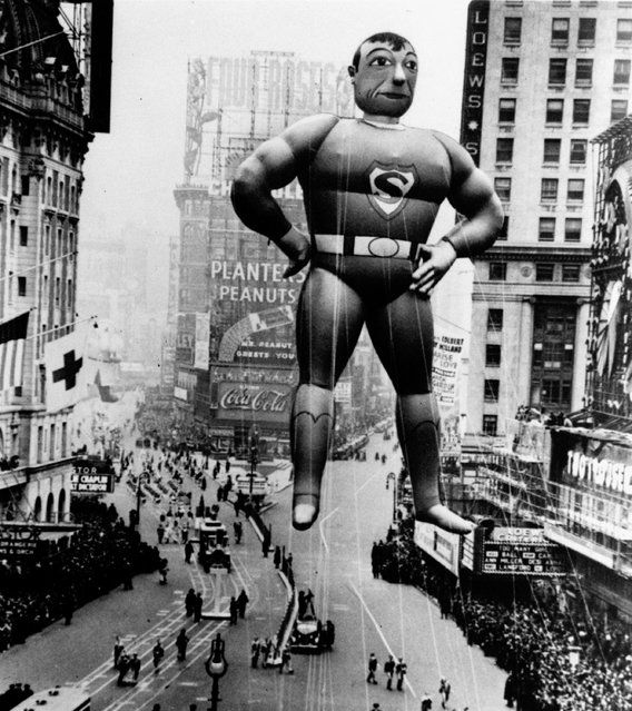 A helium inflated Superman rises over Times Square to lead the Macy's Thanksgiving Day Parade in 1940. According to Macy's, in 1929, a newly added safety valve allowed helium to slowly seep out of the balloons as they floated  above the city's streets. (Photo by AP Photo/File)