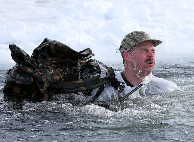A Marine plunges into the ice cold water during the ice breaking drill,  as troops take part in Exercise Hairspring 2013, which focuses on cold weather survival and warfare training for Royal Marines Commando Reservists in the mountains range near to Porsanger Garrison near Lakselv, Norway, onSaturday March 9, 2013. (Photo by Andrew Milligan/PA Wire)