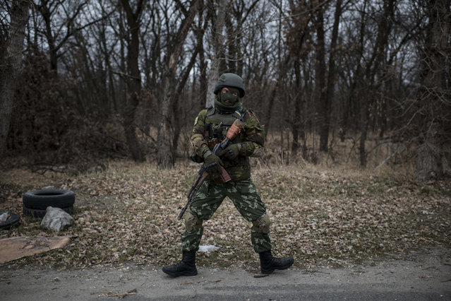 A Ukrainian serviceman shows off his dance moves to warm himself while manning a position next to a bridge over the river Siverskiy Donets damaged by explosions during a fighting between Pro-Russian rebels and Ukrainian government forces near Trehizbenka village, Luhansk region eastern Ukraine, Sunday, November 23, 2014. (Photo by Evgeniy Maloletka/AP Photo)