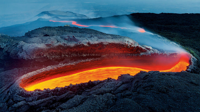 """Winner – Earth's Environments: Etna's river of fire by Luciano Gaudenzio, Italy. From a great gash on the southern flank of Mount Etna, lava flows within a huge lava tunnel, re-emerging further down the slope as an incandescent red river, veiled in volcanic gases. Gaudenzio described the vent as resembling """"an open wound on the rough and wrinkled skin of a huge dinosaur"""". (Photo by Luciano Gaudenzio/Wildlife Photographer of the Year 2020)"""