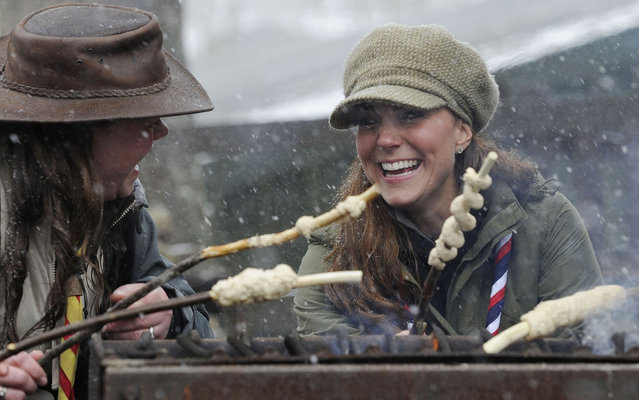 Catherine, Duchess of Cambridge joins in the preparation of campfire food during a visit to the Great Tower Scout camp at Newby Bridge in Cumbria on March 22, 2013.   The Duchess braved snowy conditions to pay a visit to the scout camp. (Photo by Andy Stenning/AFP Photo)