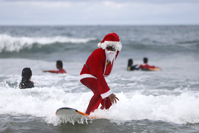 A Balinese man dressed as Santa Claus teaches orphan children how to surf at a beach in Kuta, Bali, Indonesia December 7, 2014. Every year in December a surf school in Bali held a free surf lesson to orphans as a part of Christmas celebration. (Photo by Made Nagi/EPA)