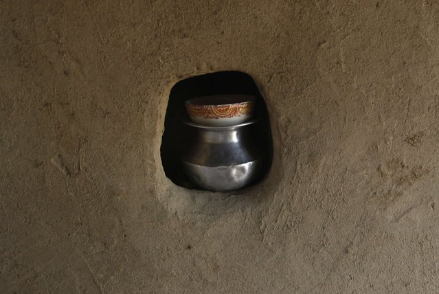 A pot of milk is covered with a bowl and placed in a hole in wall, at a home belonging to a cotton picker's family in Meeran Pur village, north of Karachi November 23, 2014. (Photo by Akhtar Soomro/Reuters)
