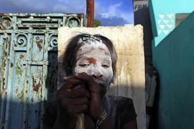"""A woman in the role of a spirit known as a """"Gede"""" looks on while holding a human bone in her hands during Day of the Dead celebrations at the National Cemetery in Port-au-Prince, Haiti, Sunday, November 1, 2015. Day of the Dead traditions coincide with All Saints Day and All Souls Day on Nov. 1 and 2. (Photo by Ricardo Arduengo/AP Photo)"""