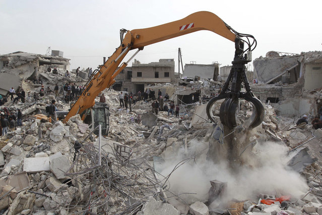An excavator is used to search for casualties under the rubble at a site hit by what activists said was a Scud missile in Aleppo's Ard al-Hamra neighborhood, on February 23, 2013. Rockets struck eastern districts of Aleppo, Syria's biggest city, killing at least 29 people and trapping a family of 10 in the ruins of their home, activists in the city said. (Photo by Muzaffar Salman/Reuters /The Atlantic)