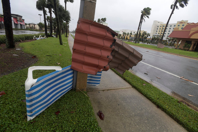 Metal roofing material is wrapped around a light pole and a palm tree (R) after the eye of Hurricane Matthew passed Daytona Beach, Florida, U.S., October 7, 2016. (Photo by Phelan Ebenhack/Reuters)