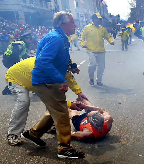 People react to a second explosion at the 2013 Boston Marathon in Boston, Monday, April 15, 2013. (Photo by John Tlumacki/AP Photo/The Boston Globe)