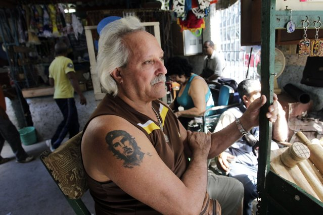 "Cuban Oscar Martinez sports a tattoo of late revolutionary hero Ernesto ""Che"" Guevara while sitting at his street stall in Havana December 17, 2014. (Photo by Reuters/Stringer)"