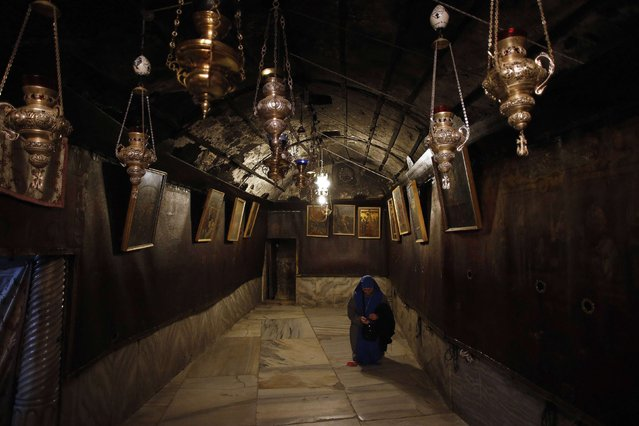 A Christian worshipper is seen inside the Grotto, where Christians believe Virgin Mary gave birth to Jesus, at the Church of Nativity ahead of Christmas in the West Bank town of Bethlehem December 17, 2014. (Photo by Ammar Awad/Reuters)