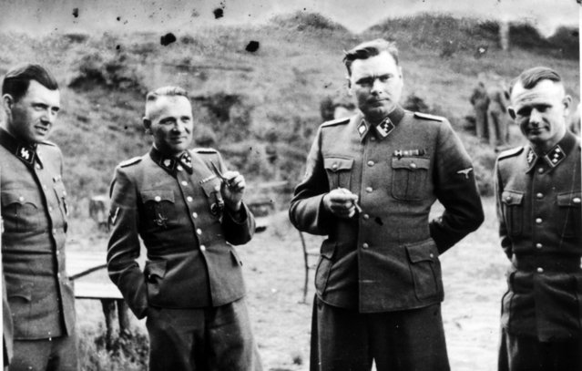 """Dr Josef Mengele (1911-1979) left, known as """"The Angel of Death"""" for the medical experiments he carried out on the inmates of Auschwitz, the German Nazi concentration. Next to him is Rudolf Hoss, Commandant of Auschwitz: Second from right is Josef Kramer, Commandant of Belsen: Right, an unidentified German officer. (Photo by Universal History Archive/Getty Images)"""