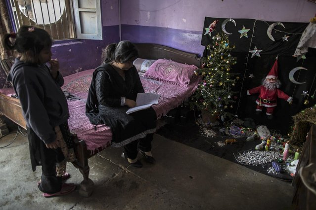 A teenager studies at her house ahead of Christmas in a Christian slum in Islamabad December 24, 2014. (Photo by Zohra Bensemra/Reuters)